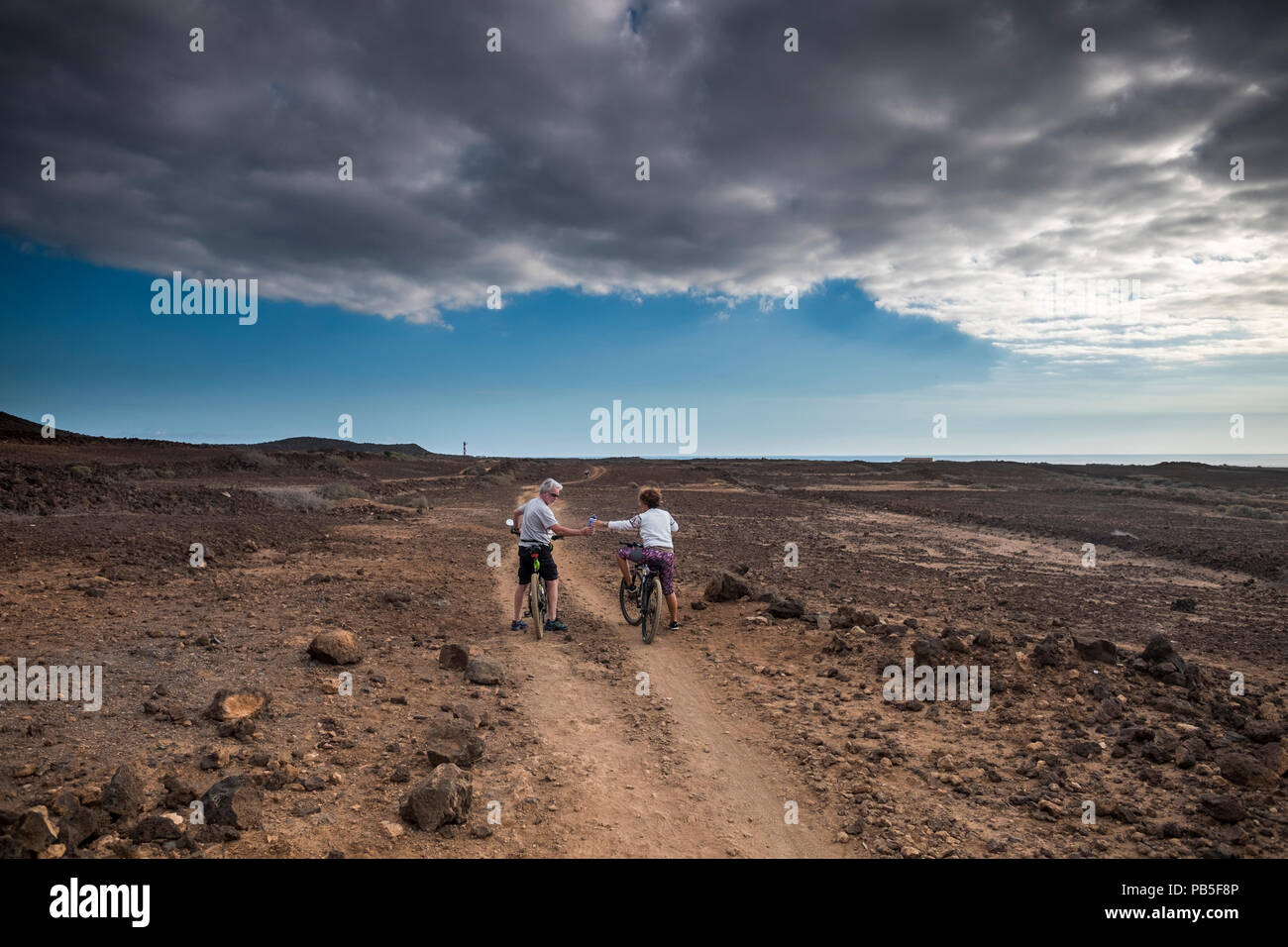 couple of rider with mountain bike follow a path in the middle of an arid desert. vacation and discover adventure in leisure sport activity for caucas - Stock Image