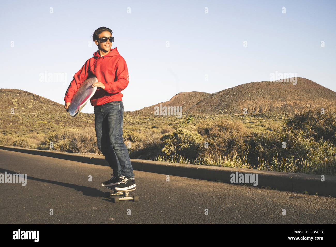 young beautiful male teenager go to the beach with the skateboard carrying a surf table for water activity in the summer. outdoor leisure for nice peo - Stock Image