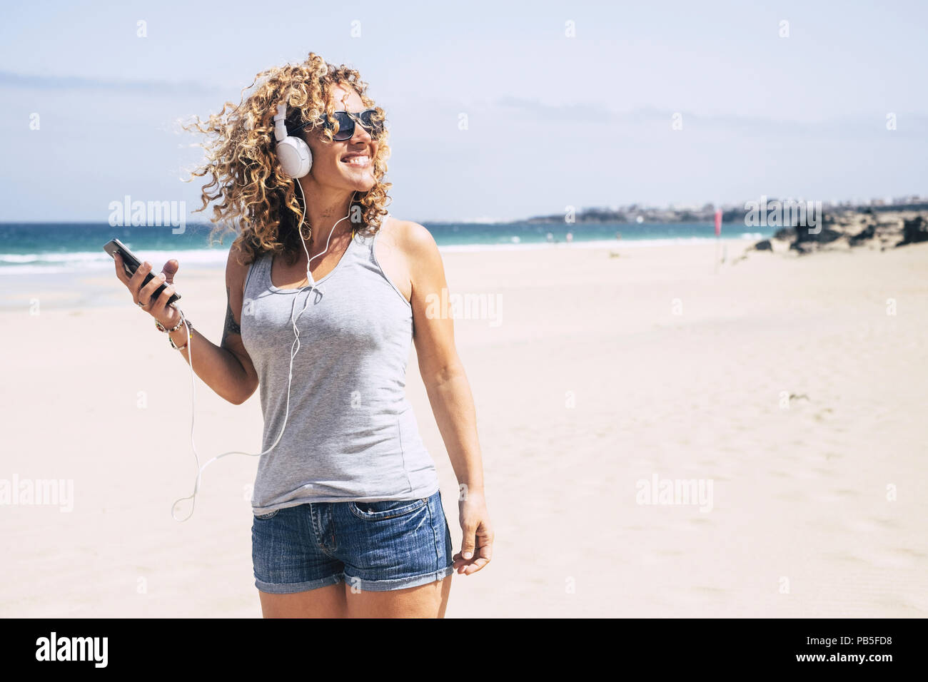 cheerful and attractive caucasian young woman enjoy the beach and the summer vacation. listening music with phone and earphones walking on the sand. h - Stock Image