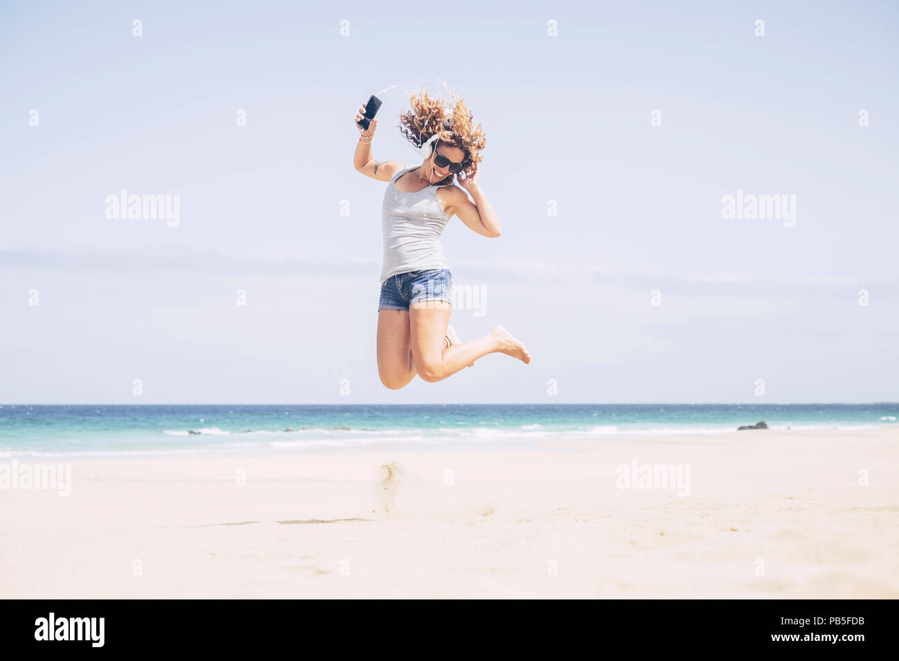cheerful and attractive caucasian young woman enjoy the beach and the summer vacation. listening music with phone and earphones jumping on the sand. h - Stock Image