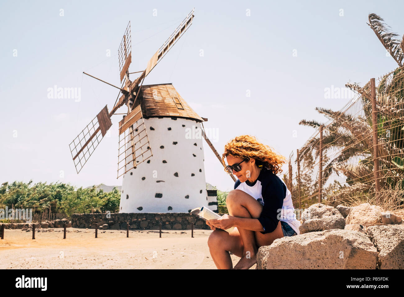 nice beautiful cheerful lady with blonde curly hair sitting under a windmill in outdoor scenic place reading a book and enjoying the leisure activity. - Stock Image