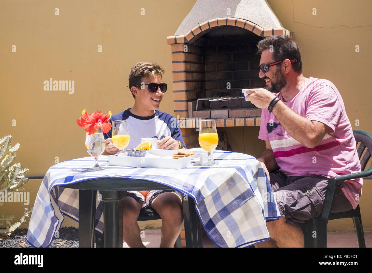 family daily happy scene with father and son caucasian people having breakfast together in the morning, summer sun for happy couple of young and old m Stock Photo