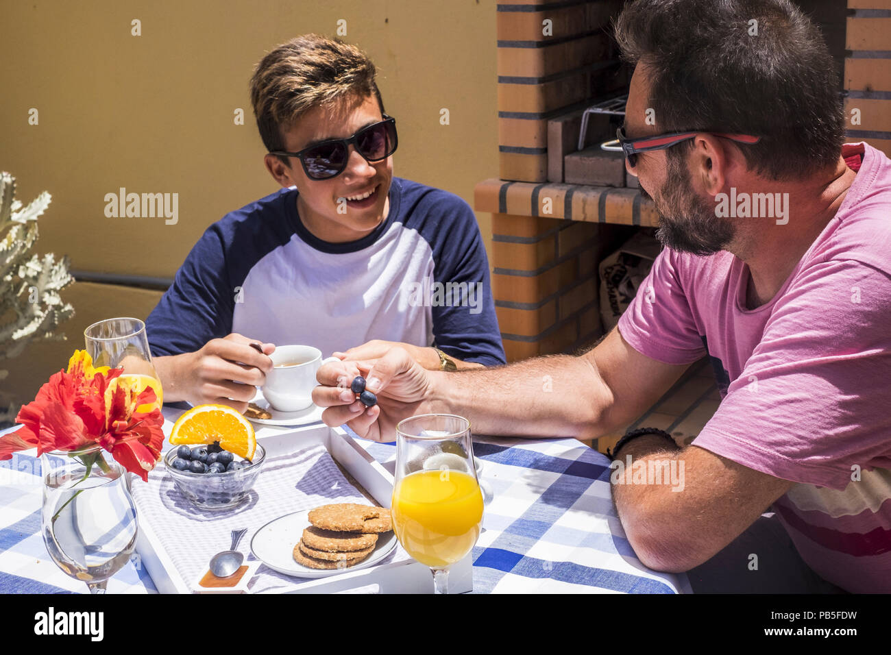family daily happy scene with father and son caucasian people having breakfast together in the morning, summer sun for happy couple of young and old m - Stock Image