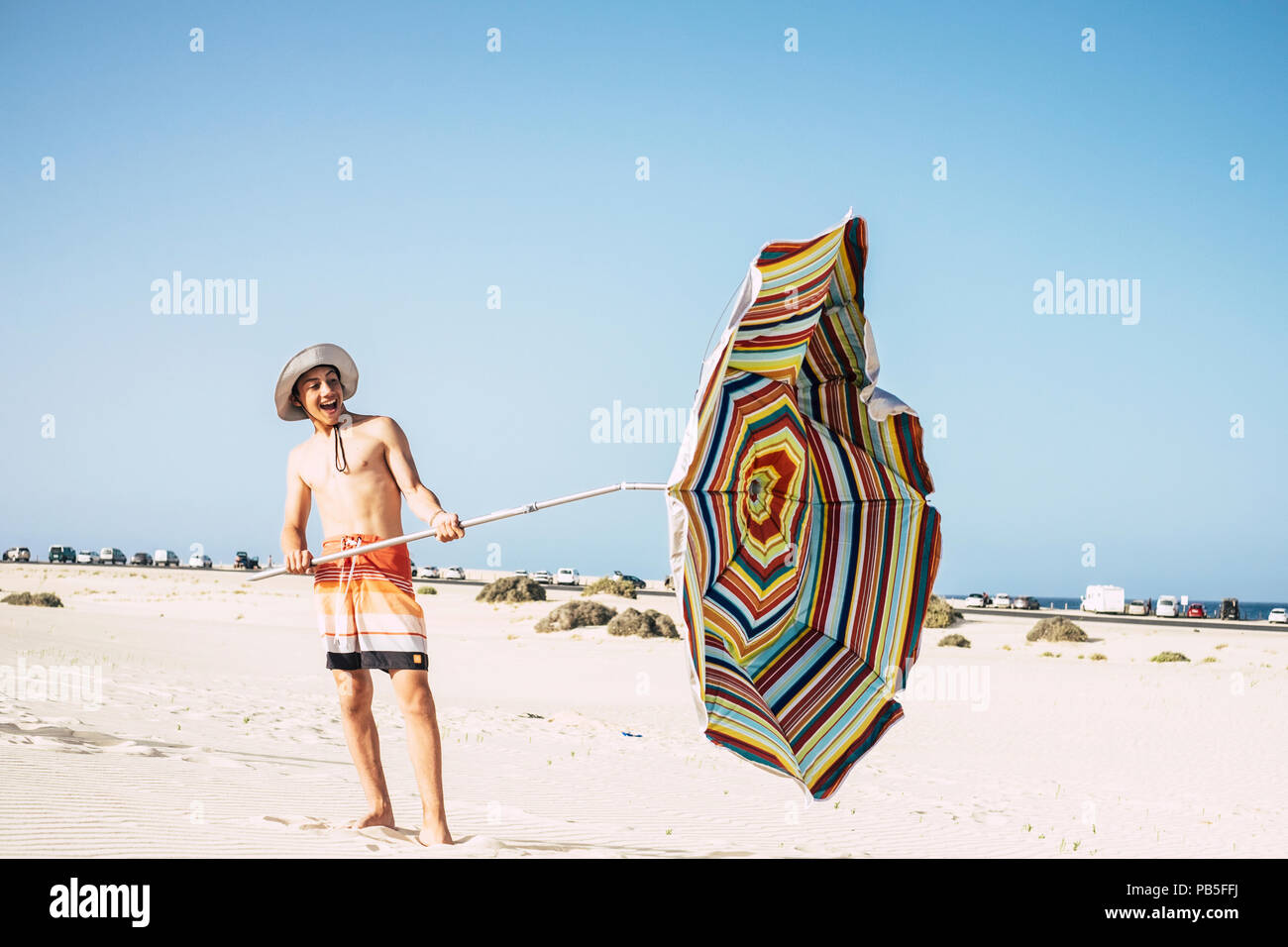 young male caucasian teenager play with umbrella sun and wind in a sandy paradise beach. smile and have fun enjoying the holiday and the warm weather  - Stock Image