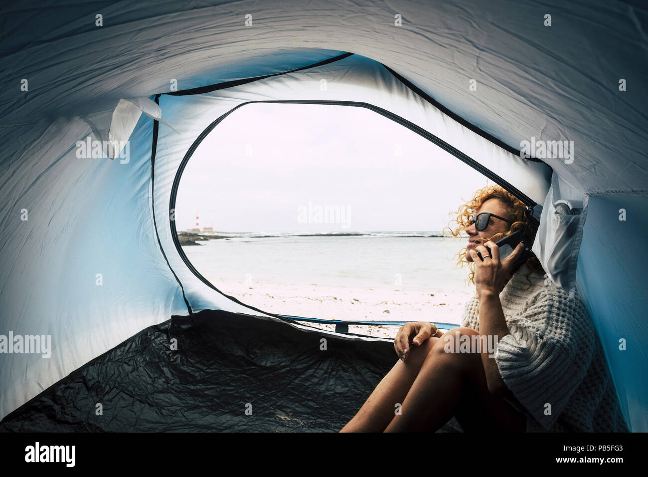 beautiful happy middle age caucasian woman smile and enjoy camping on the beach near the ocean waves. use phone to connect internet and call with frie - Stock Image