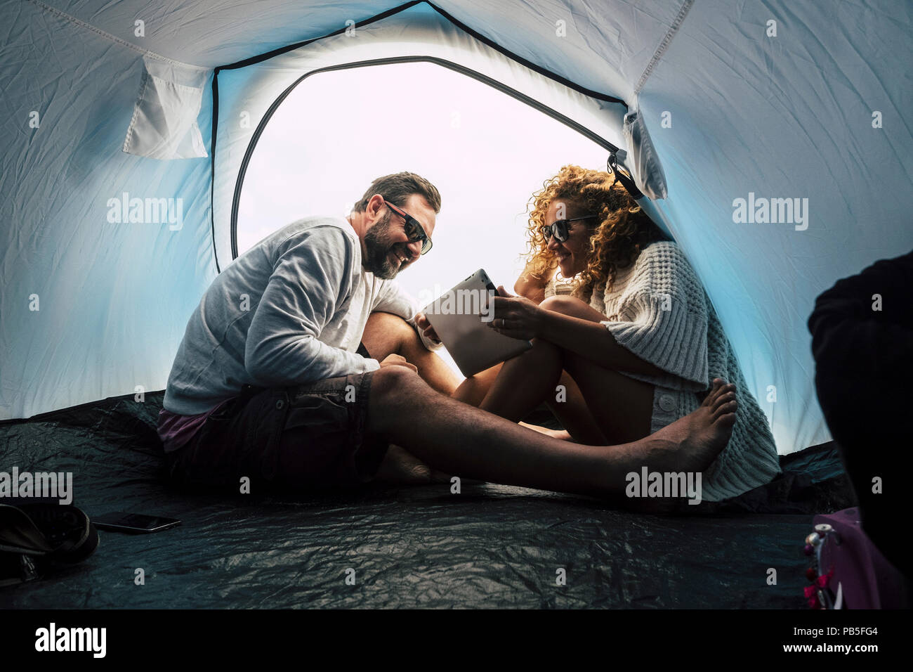 happy young middle age couple married and in relationship enjoy the camping inside the tent and use tablet internet technology. love and friendship fo - Stock Image