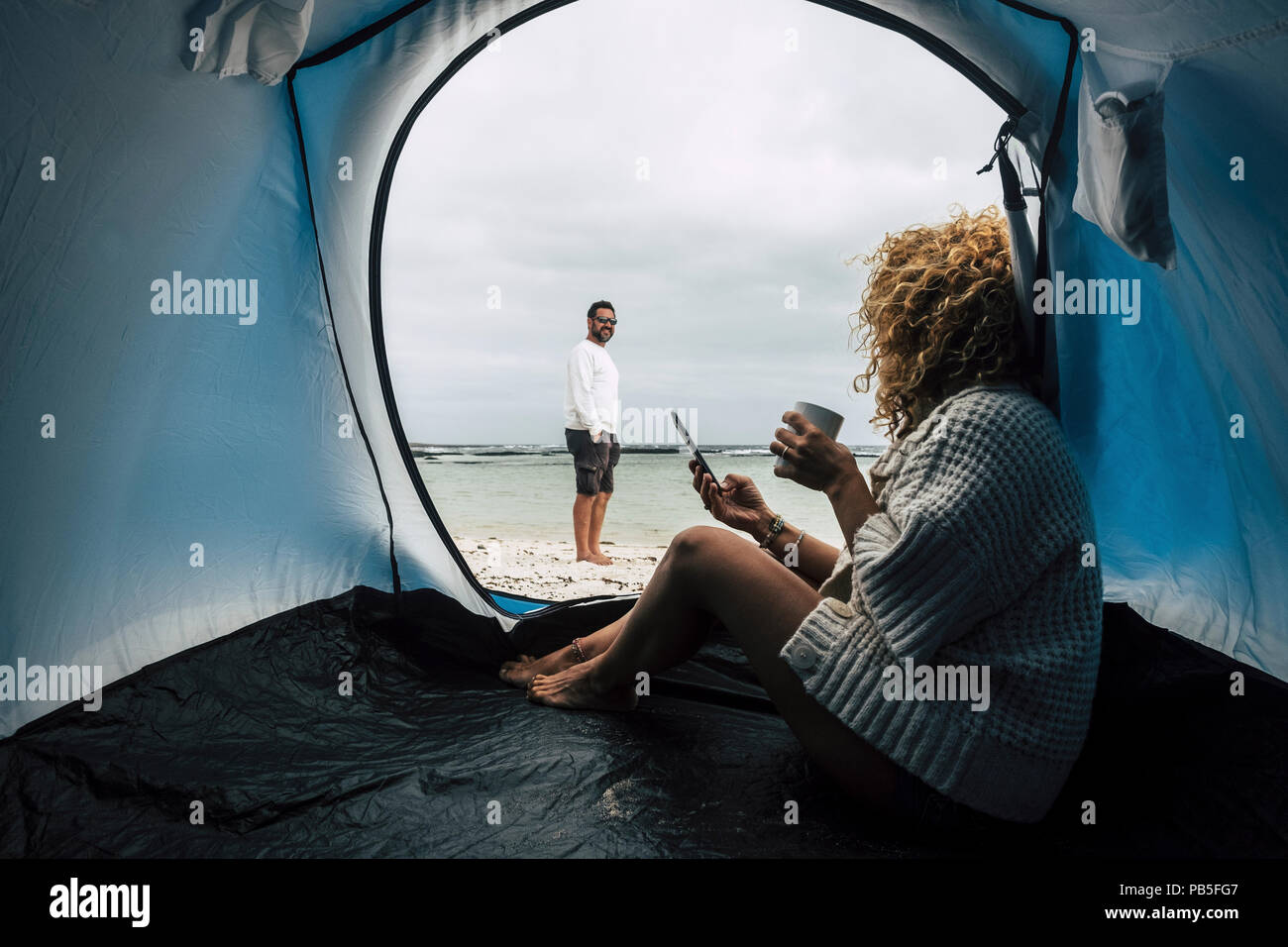 couple of caucasian traveler people camping on the beach near the ocean waves, paradise vacation alternative lifestyle with tiny house and enjoying th Stock Photo