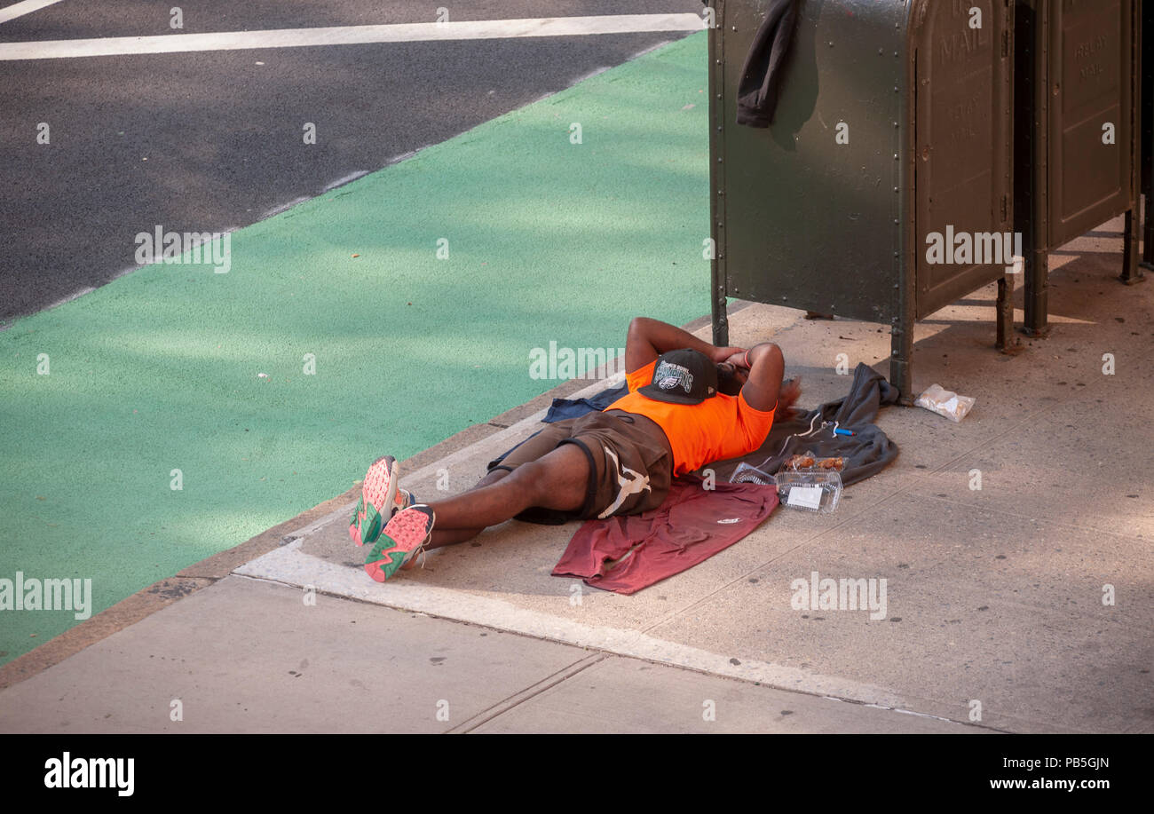 A individual sleeps on the sidewalk in the Chelsea neighborhood of New York on Wednesday, July 18, 2018. (© Richard B. Levine) - Stock Image