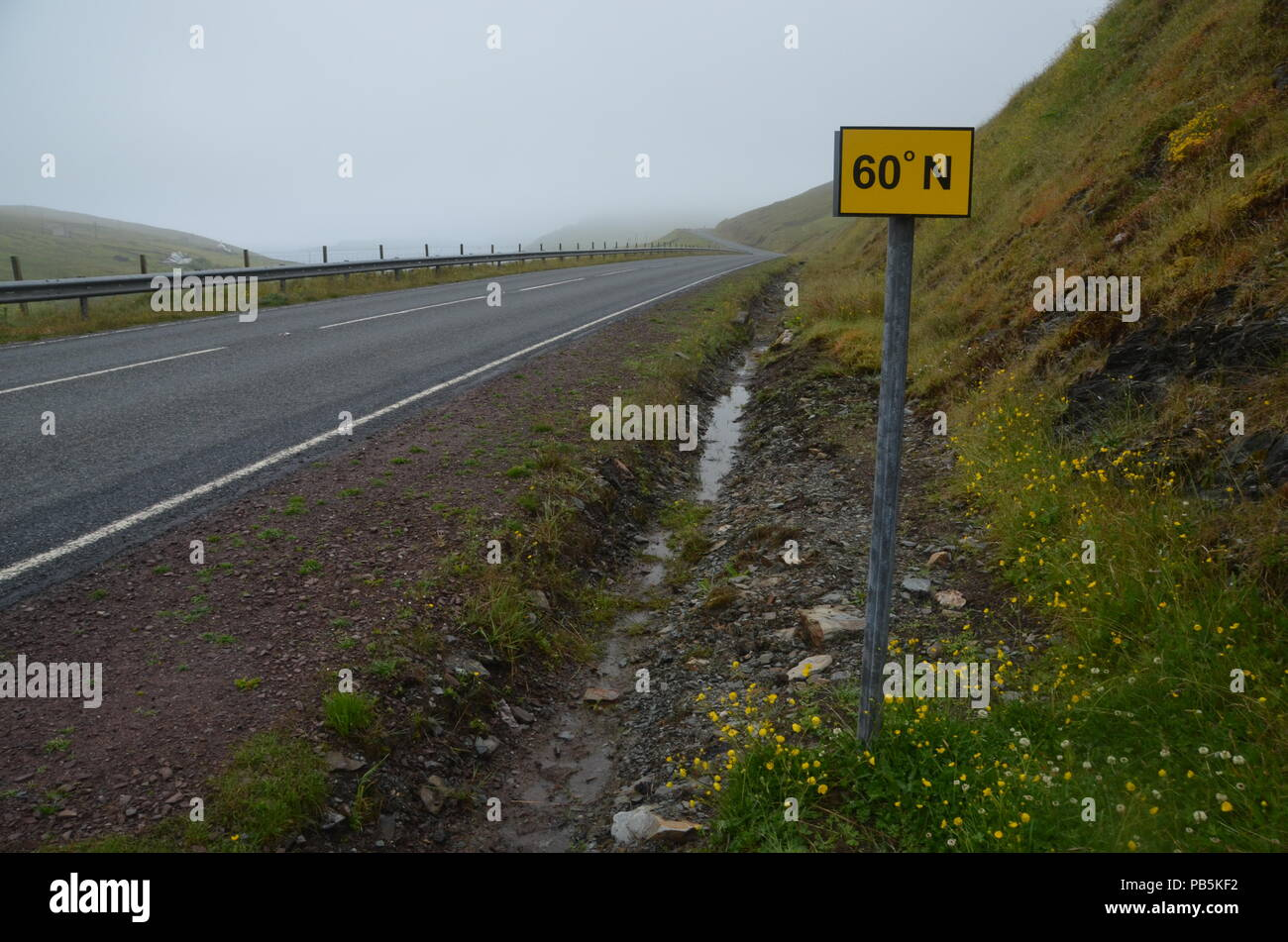 A sign marking the point where the A970 road crosses the 60 degrees north line of latitude, in Shetland, British Isles, UK - Stock Image