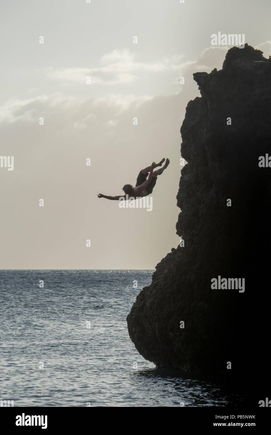 Maui, Hawaii.  Cliff jumper. Man jumping off cliff into the Pacific ocean. - Stock Image