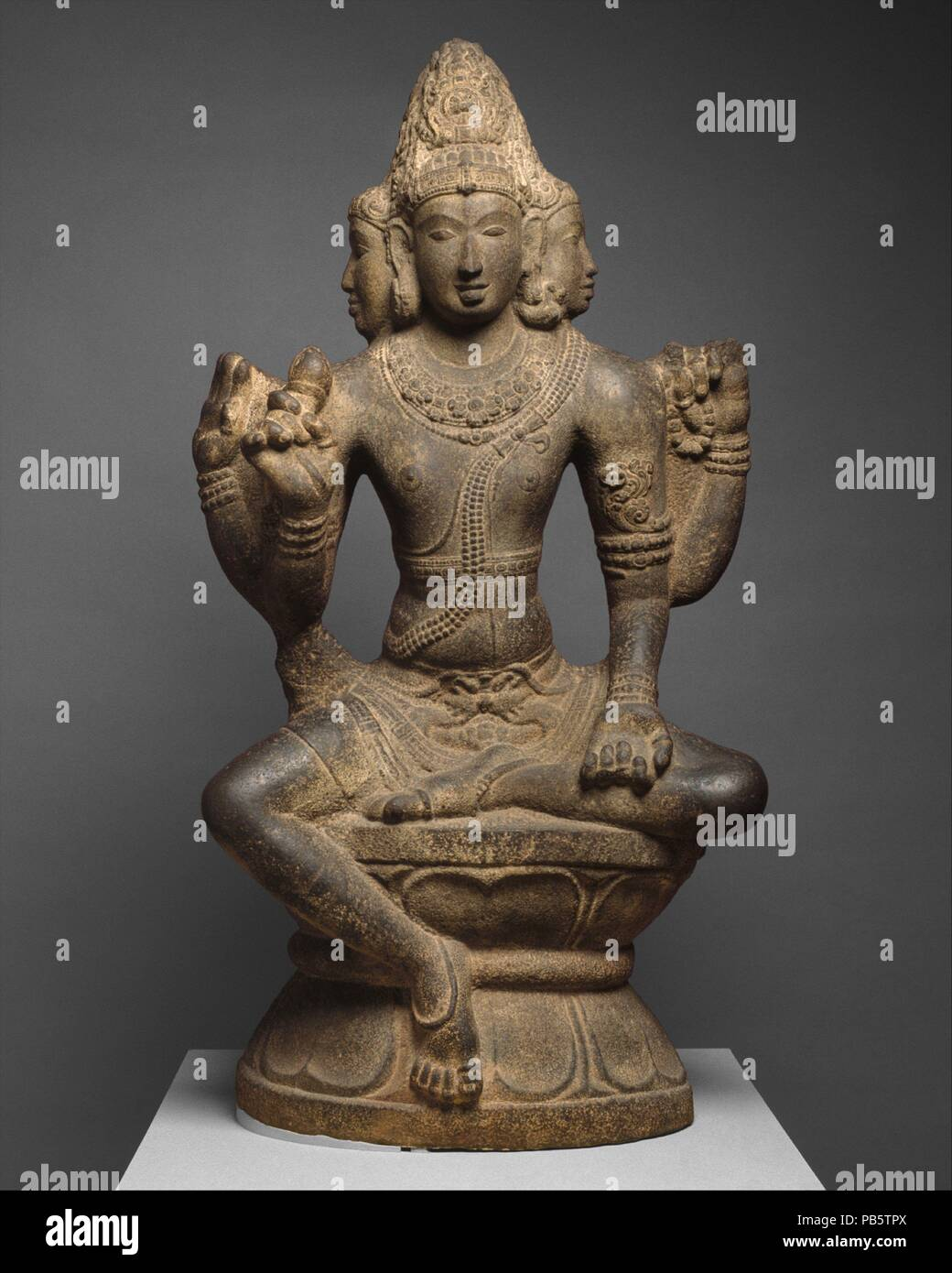 Shiva as Mahesha. Culture: India (Tamil Nadu). Dimensions: H. 58 in. (147.3 cm); W. 32 in. (81.3 cm); D. 16 in. (40.6 cm). Date: 10th century.  This statue is part of a group of unusual large stone carvings in the round from the Chola period. They all portray the same deity, long identified as Brahma but now thought to be Mahesha, a form of Shiva. Shiva's worshipers believe that he manifests himself in three stages, which move from the abstract to the concrete--symbolized by the undecorated linga (shaft); the linga with one or more faces emerging from it; and, finally, Mahesha. From him are bo Stock Photo