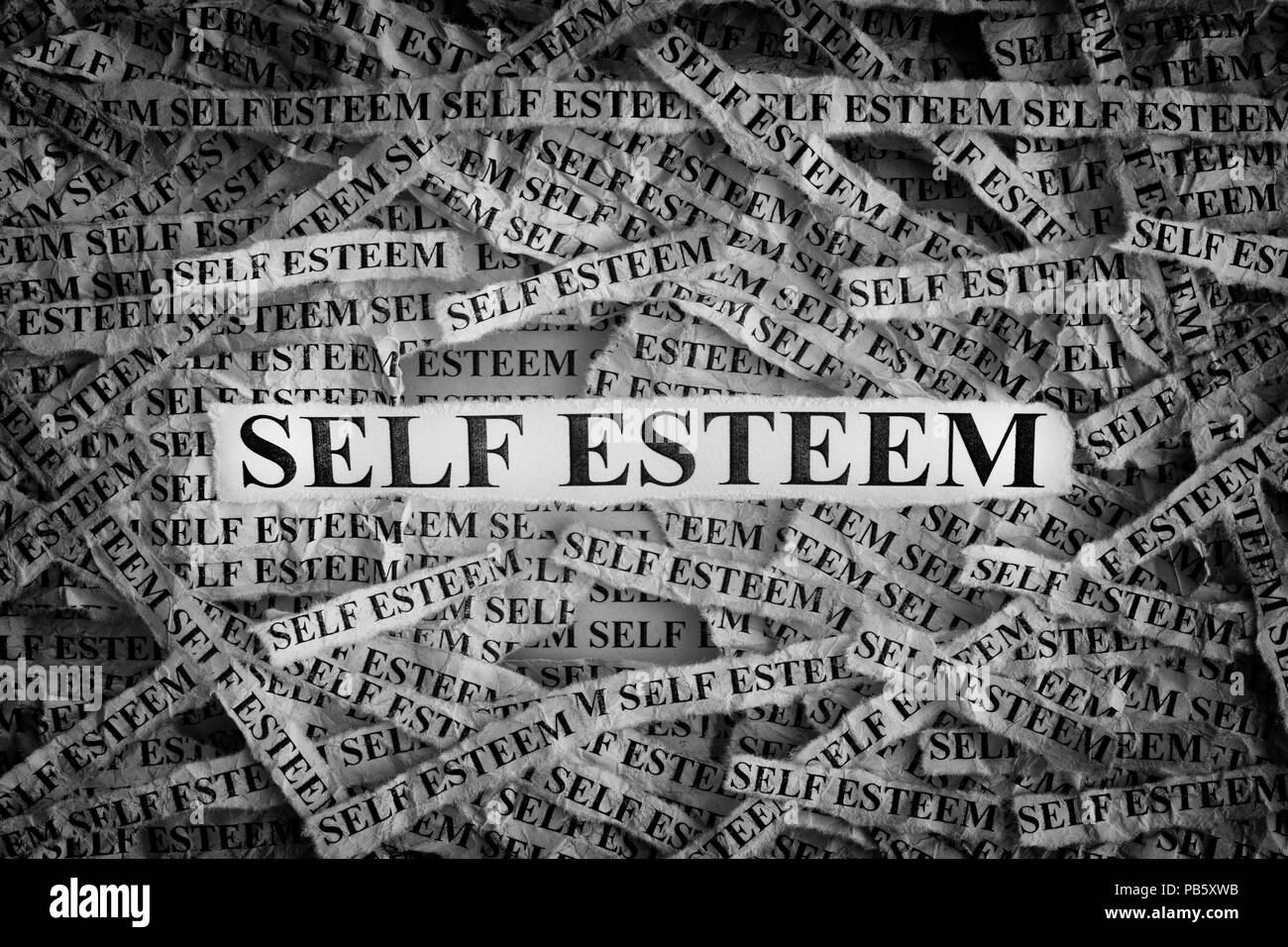 Self Esteem. Torn pieces of paper with the words Self Esteem. Concept Image. Black and White. Closeup. - Stock Image