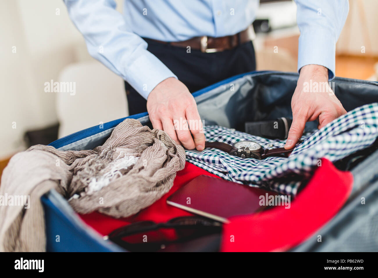 Man preparing for business travelling. Open traveler's bag with passport, clothing and accessories. Travel and vacations concept. - Stock Image