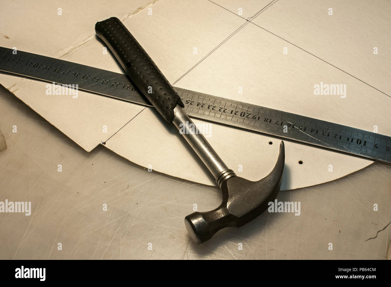 Hammer, metal ruler and cardboard cuts as tools in workshop production of leather goods Stock Photo