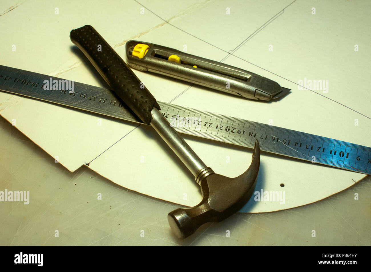 Hammer, metal ruler, cutter knife and cardboard cuts as tools in workshop production of leather goods Stock Photo