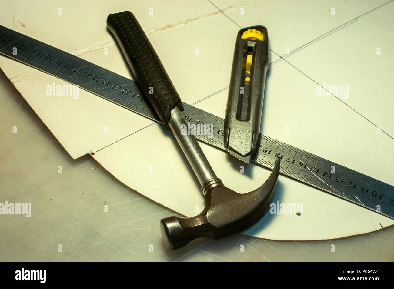 Hammer, metal ruler, cutter knife and cardboard cuts as tools in workshop production of leather goods - Stock Image