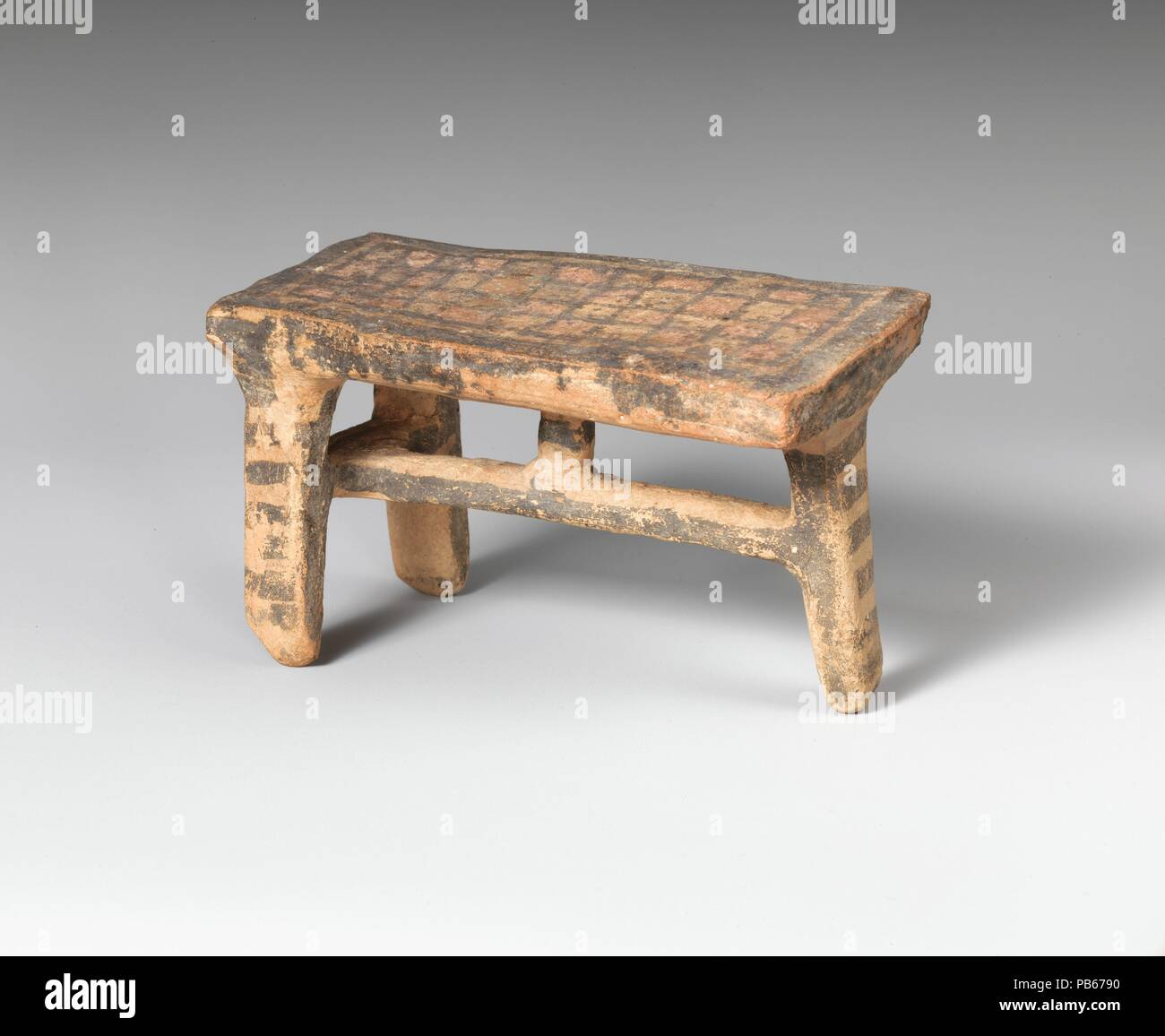 Terracotta table. Culture: Cypriot. Dimensions: H. 2 7/8 in. (7.3 cm). Date: ca. 600-480 B.C..  This is one of three known Cypriot models of tables. The rectangular top is supported on three legs, a convention familiar from the Aegean region and the Near East as well. The checkerboard pattern on the top is interesting; it recalls the shrouds of Attic geometric funerary vases and raises the question whether these tables might have been used as biers. Museum: Metropolitan Museum of Art, New York, USA. - Stock Image