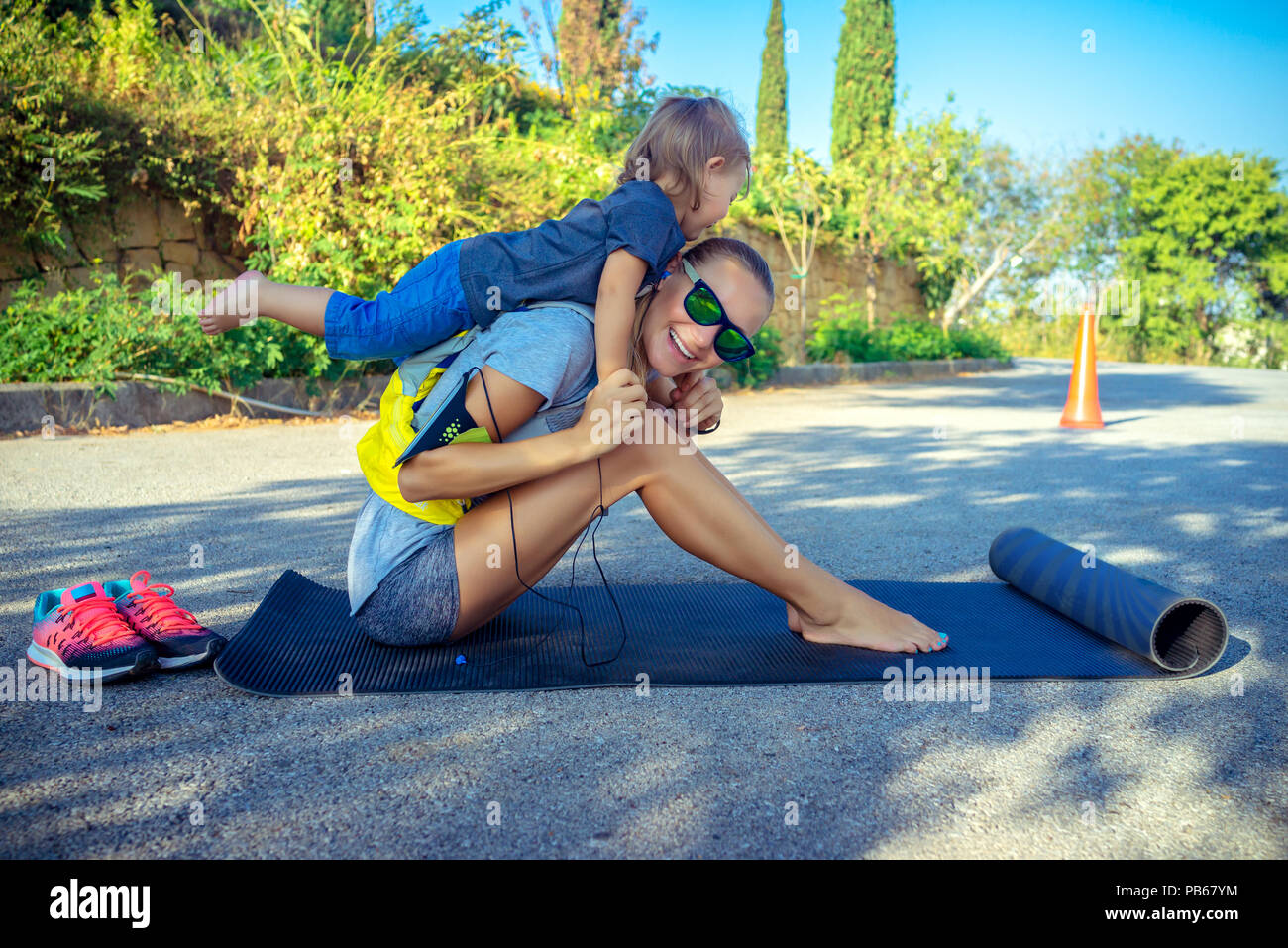 Healthy family life, cute cheerful baby boy plays piggy back and helps her to do stretching, beautiful woman with her little son doing sport excercise - Stock Image
