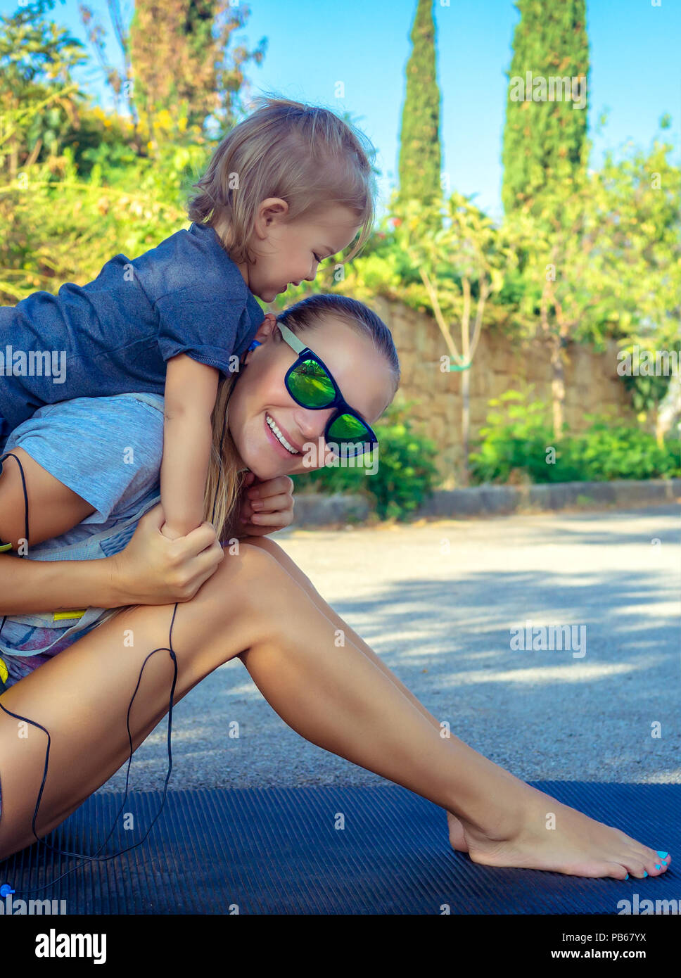 Portrait of a beautiful mom and her son playing sports games in the park on sunny summer day, happy active childhood, good loving family concept - Stock Image