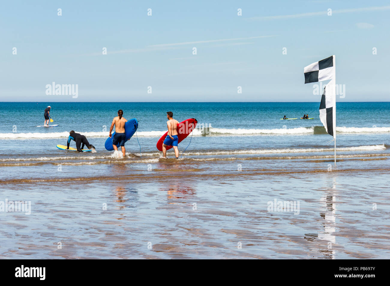 Surfers carrying their boards to the sea on a hot day at Westward Ho!, Devon, UK - Stock Image