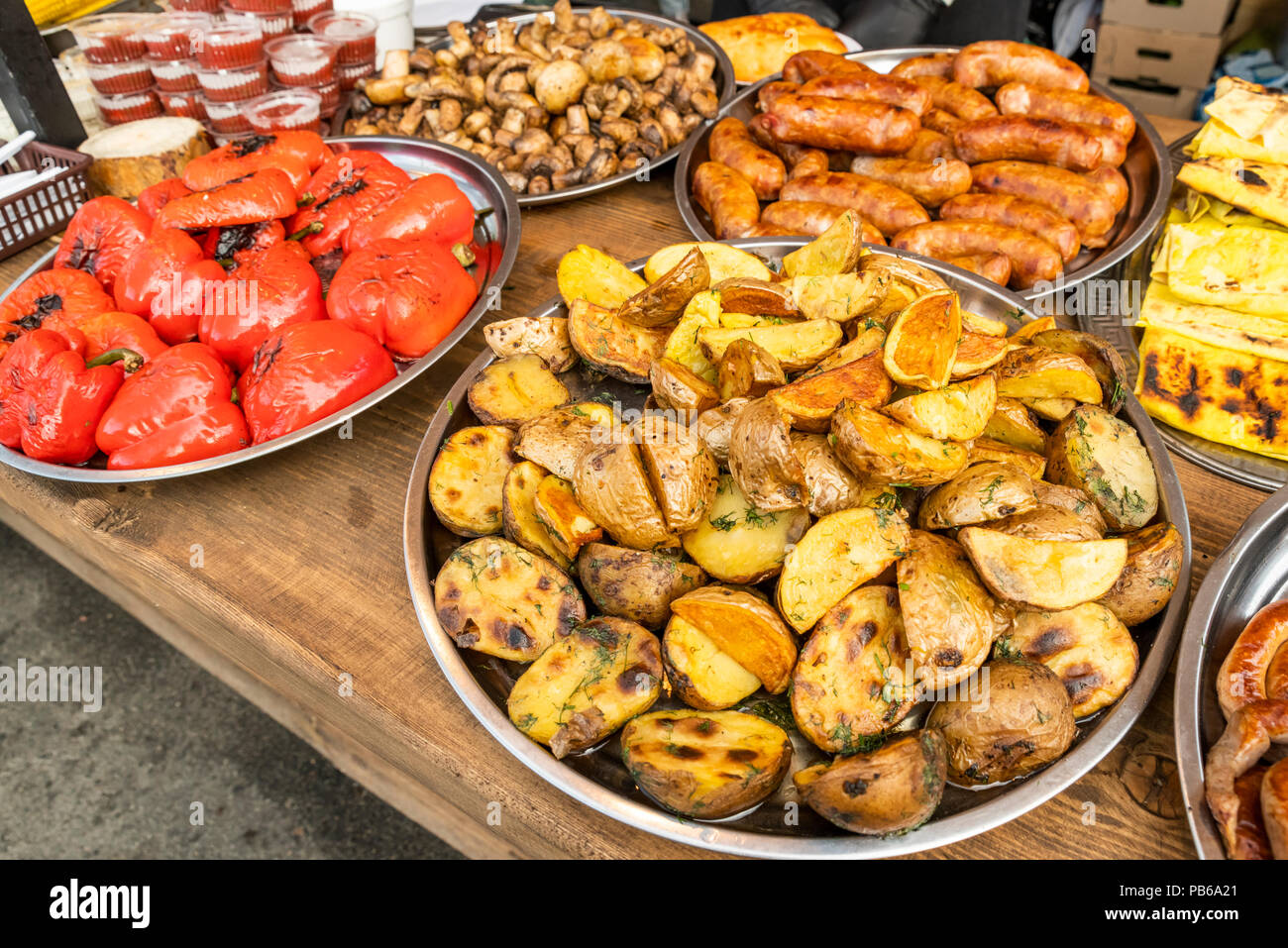Fried Potatoes Sliced In Large Slices Laid Out On A Large Metal Plate With Fried Sausage And Baked Vegetables And Ketchup In Plastic Containers On A Stock Photo Alamy