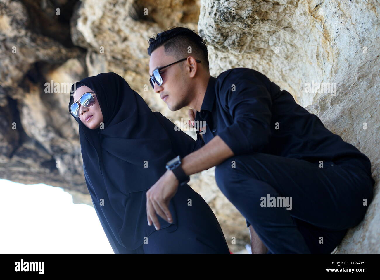Muslim couple in the mountains rock with black dress stock image