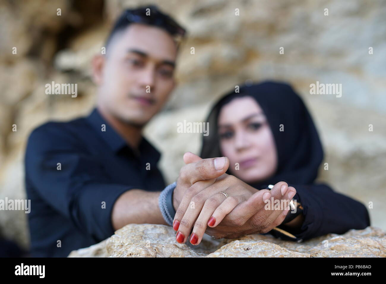 Muslim Couple holding hand in the mountains Rock with Black Dress - Stock Image