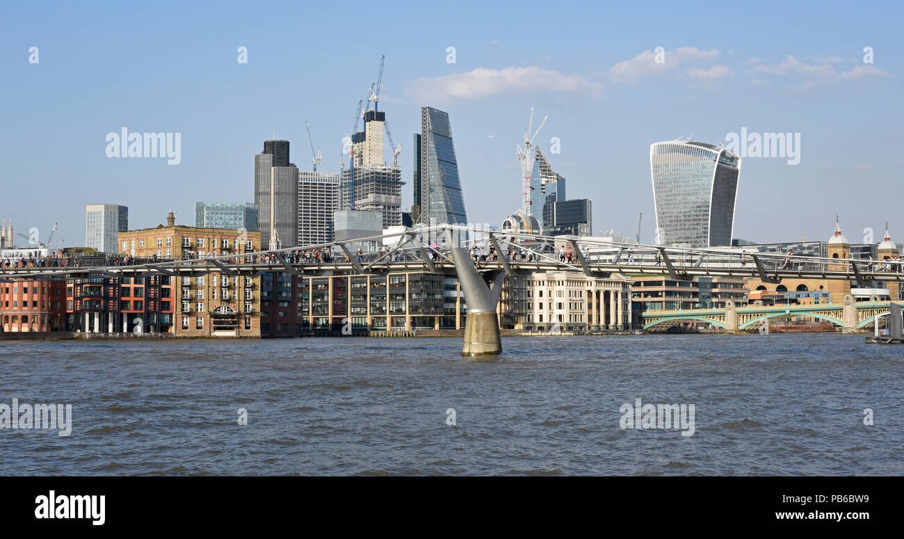 Views of the London Square Mile and the Millennium Bridge in London on a sunny April evening - Stock Image