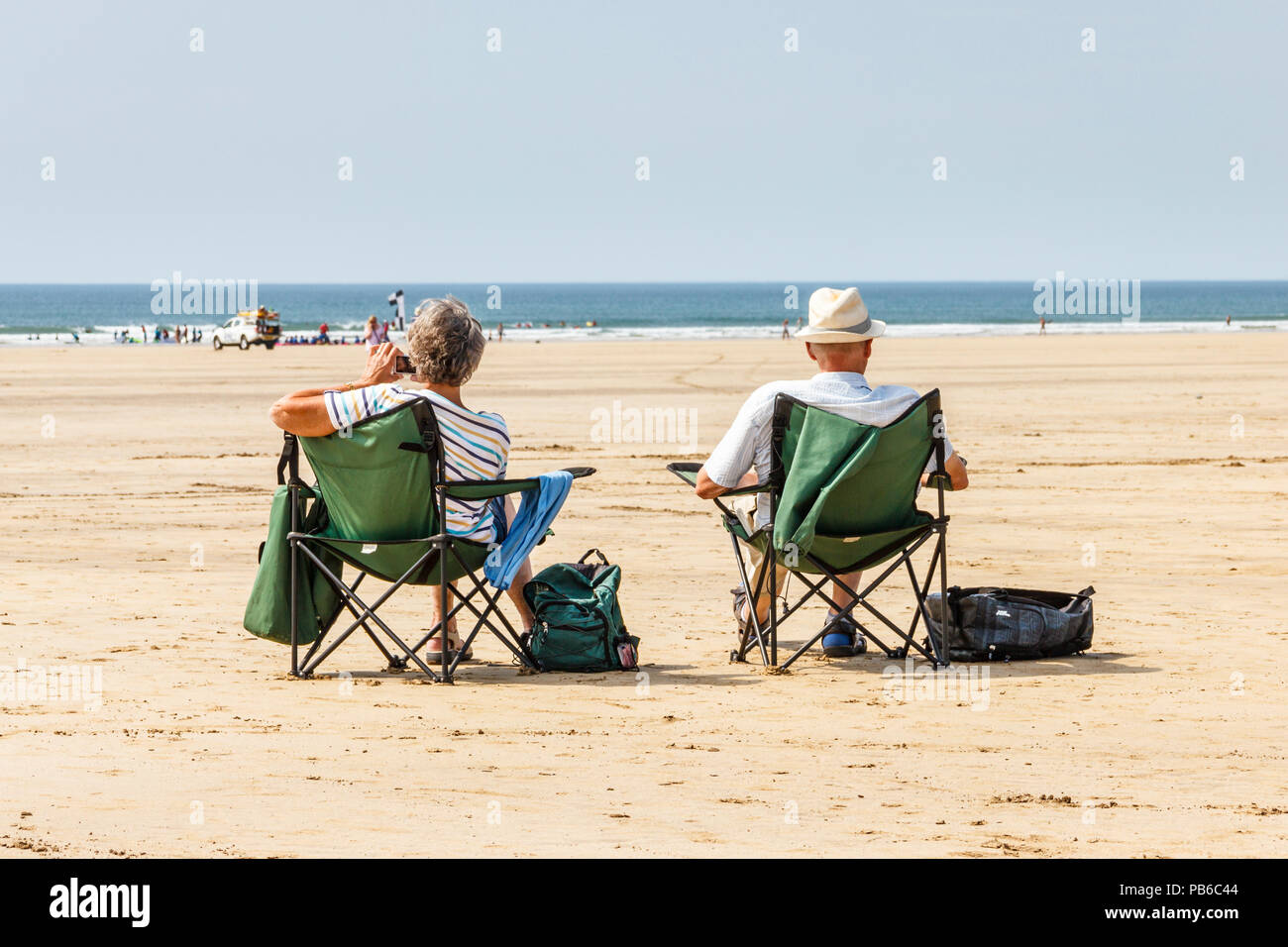 Two older holidaymakers (man and woman) in beach chairs seeking sun and sea as the summer heatwave continues, Westward Ho!, Devon, UK - Stock Image
