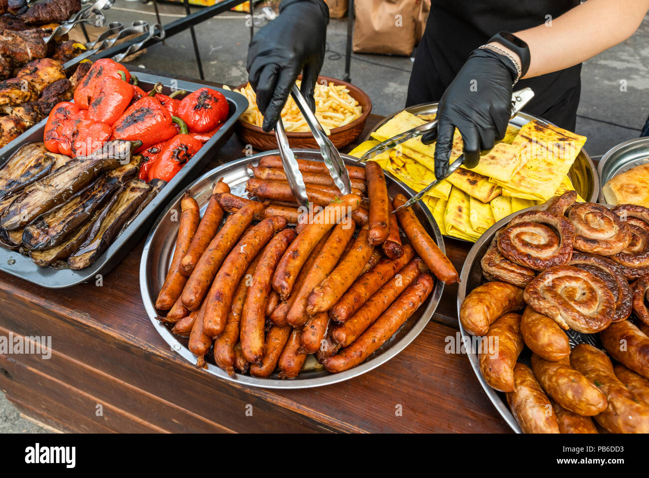 grilled sausages that are laid out on a large metal plate on a table - Stock Image