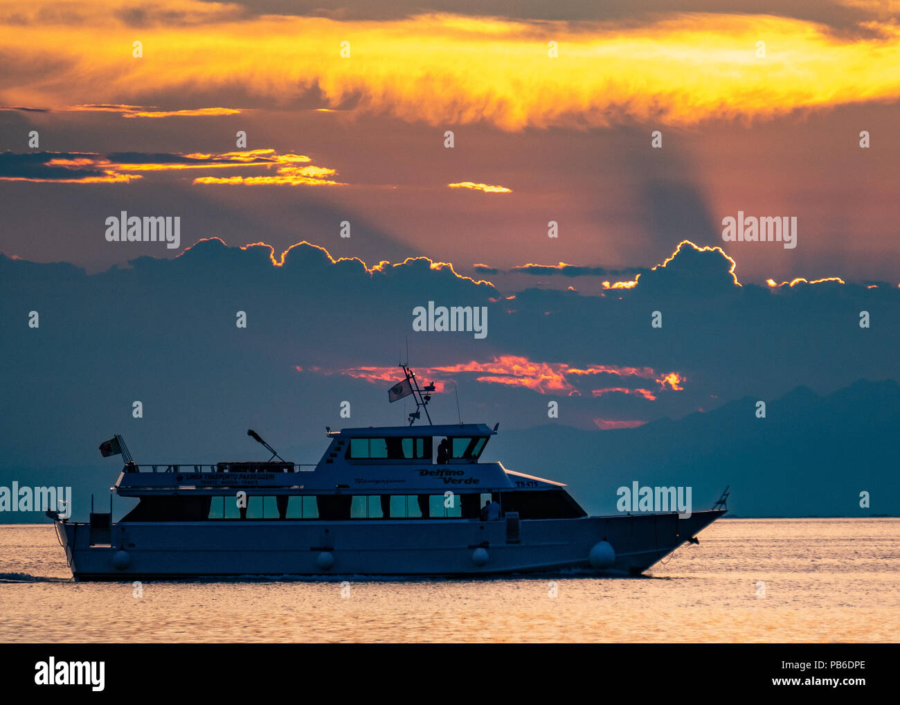 "Trieste, Italy, 26 July 2018.  An empty ""Delfino Verde"" passenger ship departs from the port of Trieste at sunset.  Photo by Enrique Shore Stock Photo"