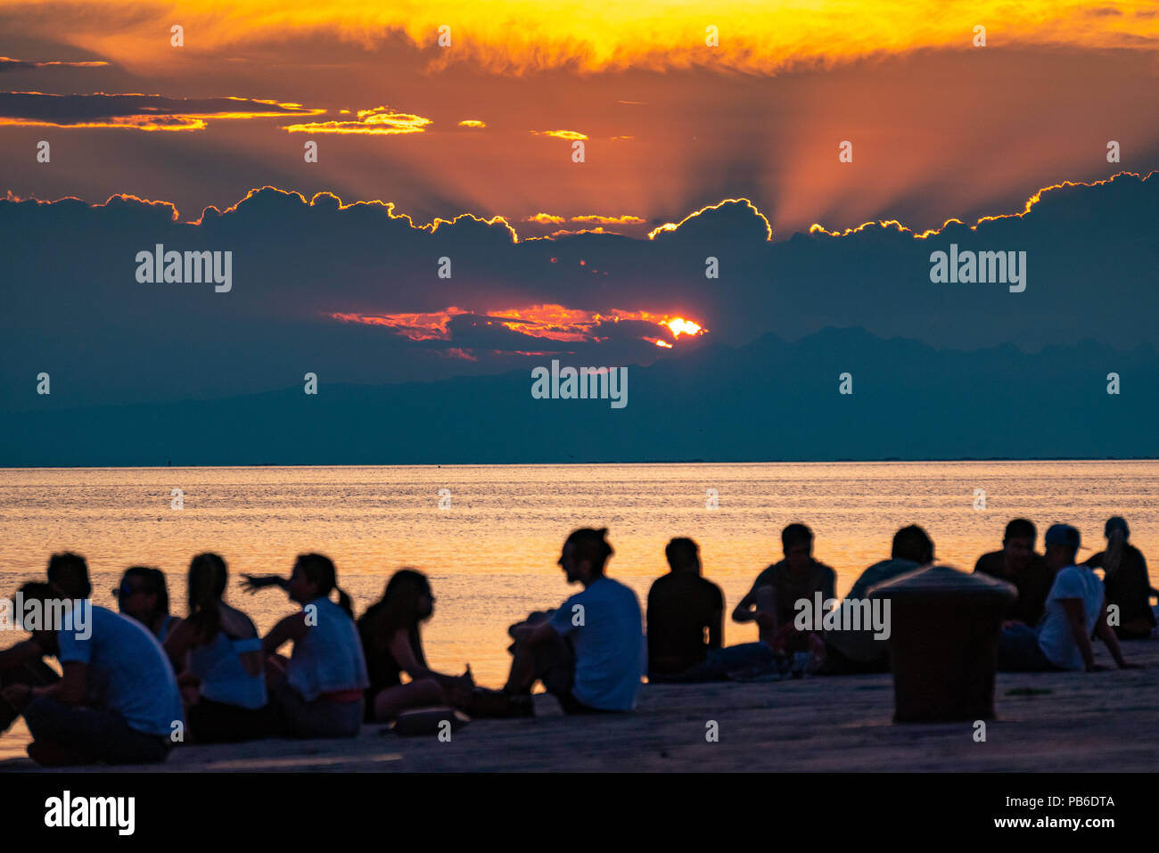 Trieste, Italy, 26 July 2018.  People enjoy the sunset from the iconic  Molo Audace (Audace Pier) in the northern Italy city of Trieste.  The 246-mete - Stock Image