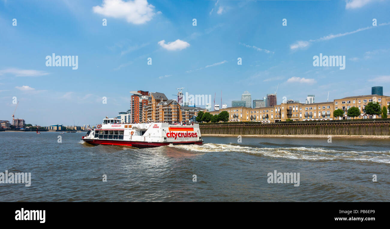 City cruises sightseeing boat 'Millenium Dawn' takes passengers along the River Thames past the Isle of Dogs; Canary Wharf in background. - Stock Image