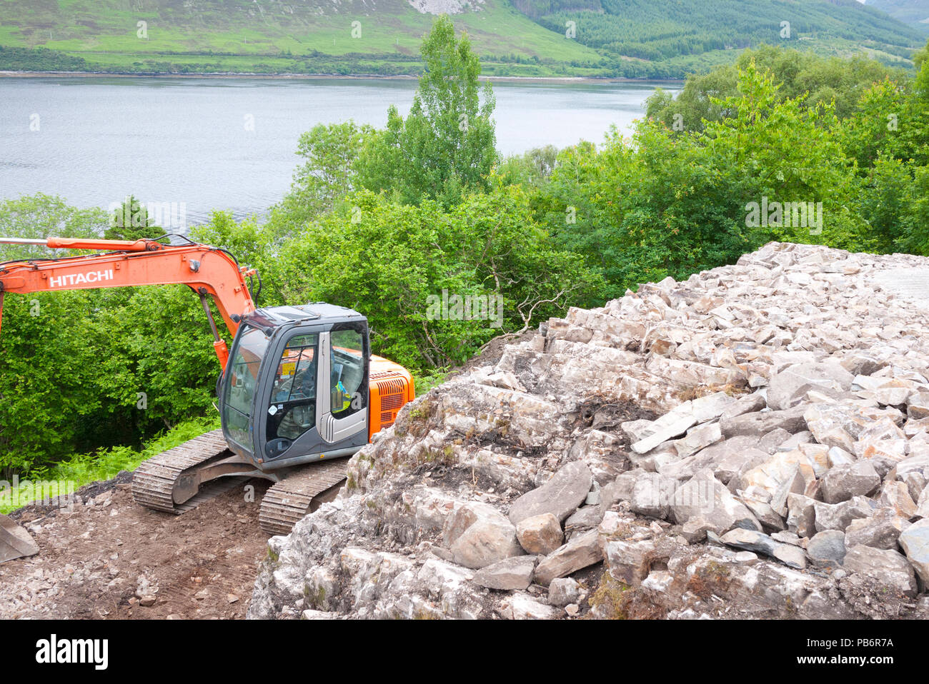 JCB excavating a plot for housing high up over Loch Broom,Wester-Ross,Highland, Scotland,UK. - Stock Image