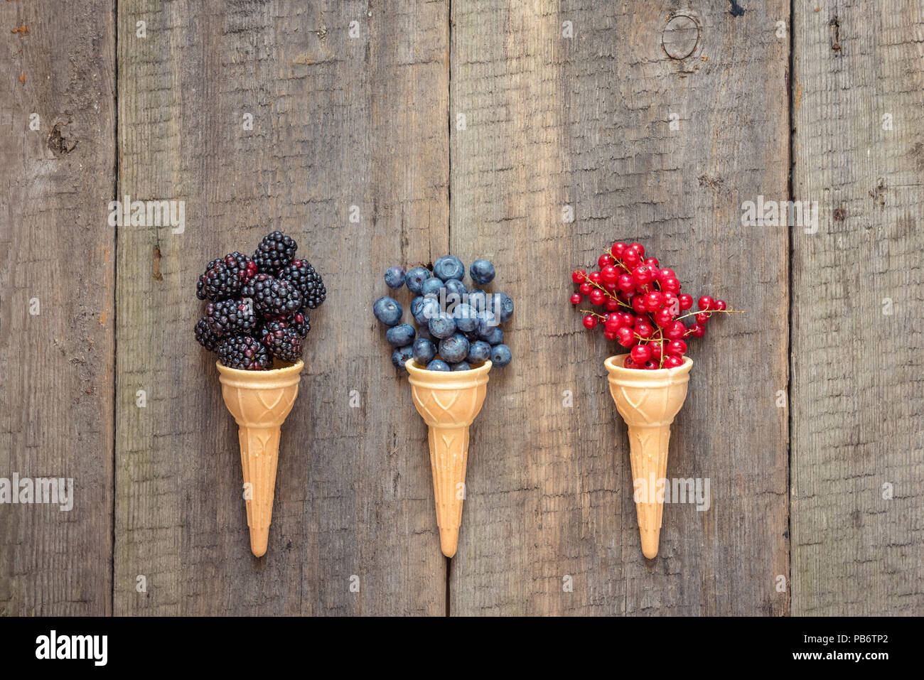 Fresh fruit and berries in ice cream cones. Healthy summer food concept.Top view with space for text. - Stock Image