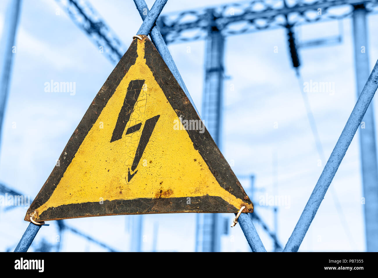 Old aged rusty triangle metal plate with High voltage warning sign. Power station with transformers and electricity distribution lines. Keep out Stock Photo