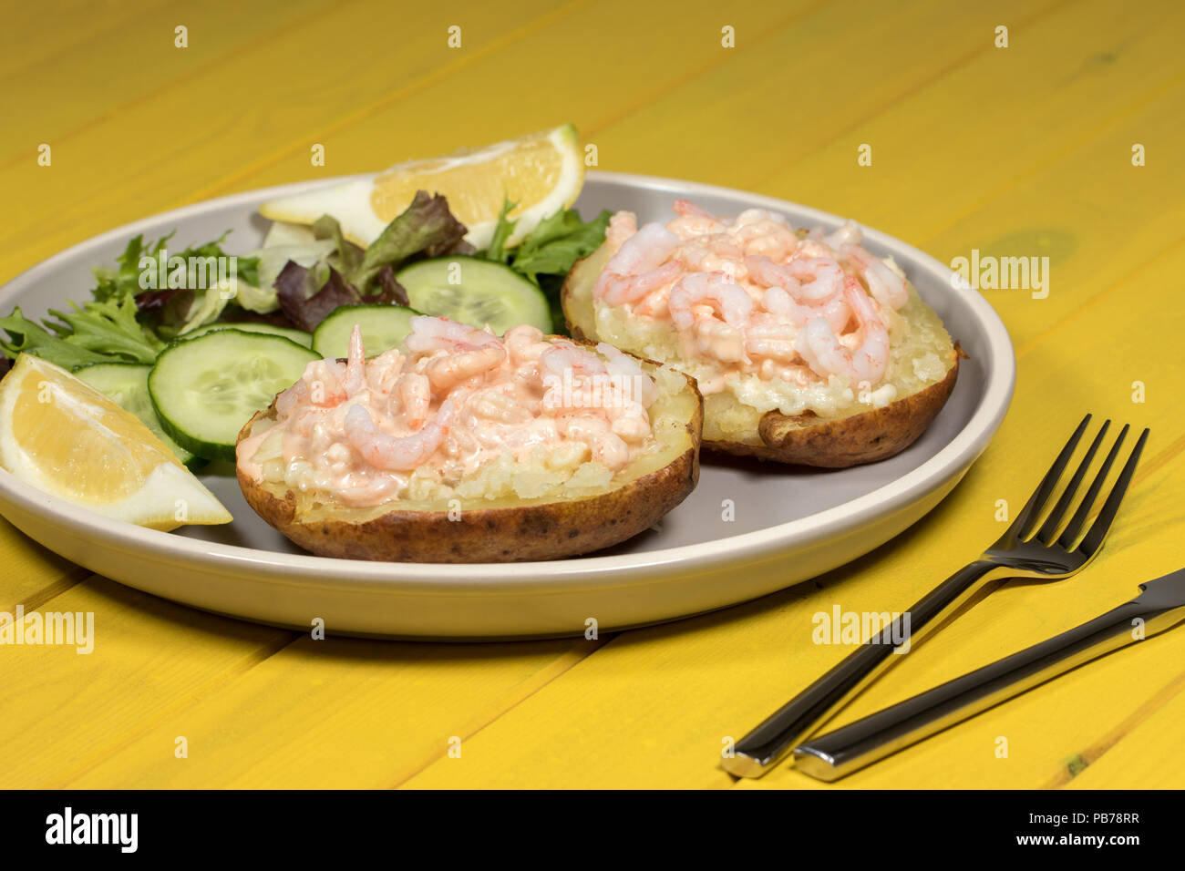 Classic healthy slimming food. Prawn on jacket potato with lettuce leaf salad. Nutritional low-calorie seafood meal of prawns in Marie Rose sauce. - Stock Image