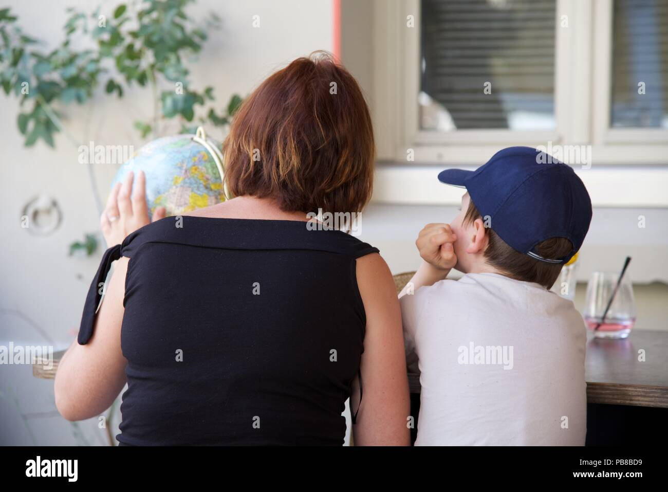 Mother and son: a mother and son regard the spinning globe they have just bought at a French brocante as they sit in the shade of a restaurant - Stock Image