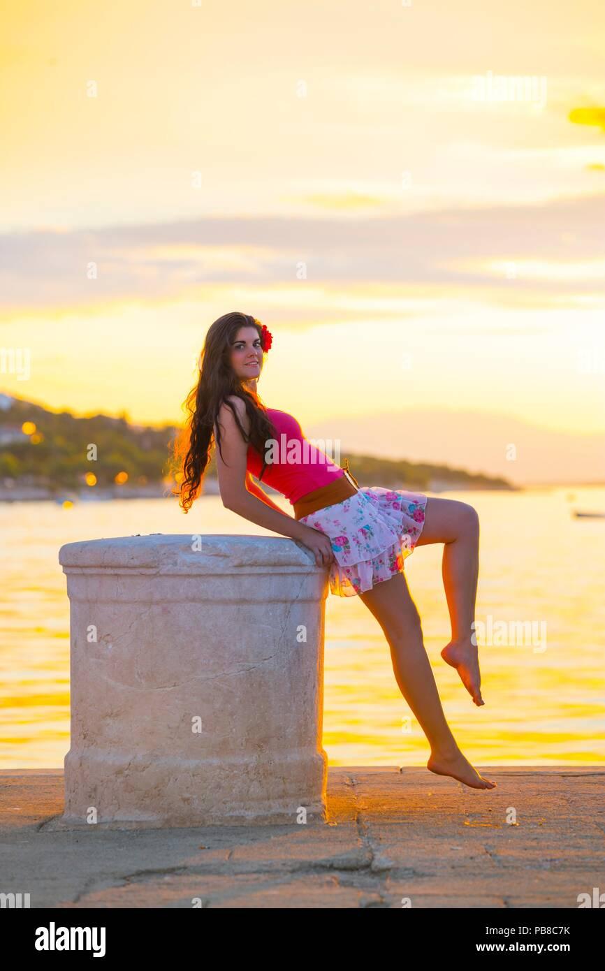 Teenager female against sunset background happy smiling leaning against big harbor bollard - Stock Image