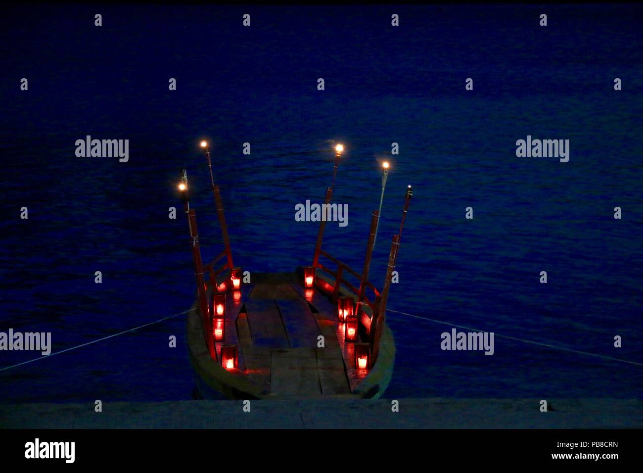 Candle and torch lit small wooden boat on a lake - Stock Image