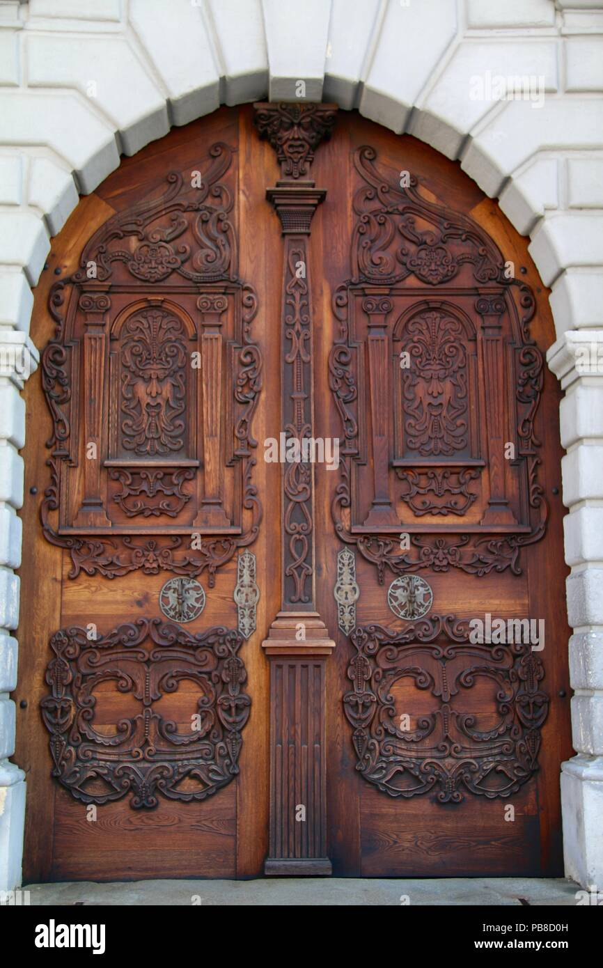 Carved and polished double wooden arched doors - Stock Image