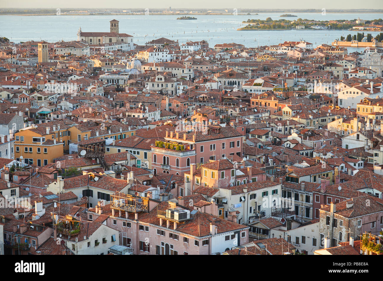 Elevated view of Venice with roofs buildings and sea before sunset, Italy Stock Photo