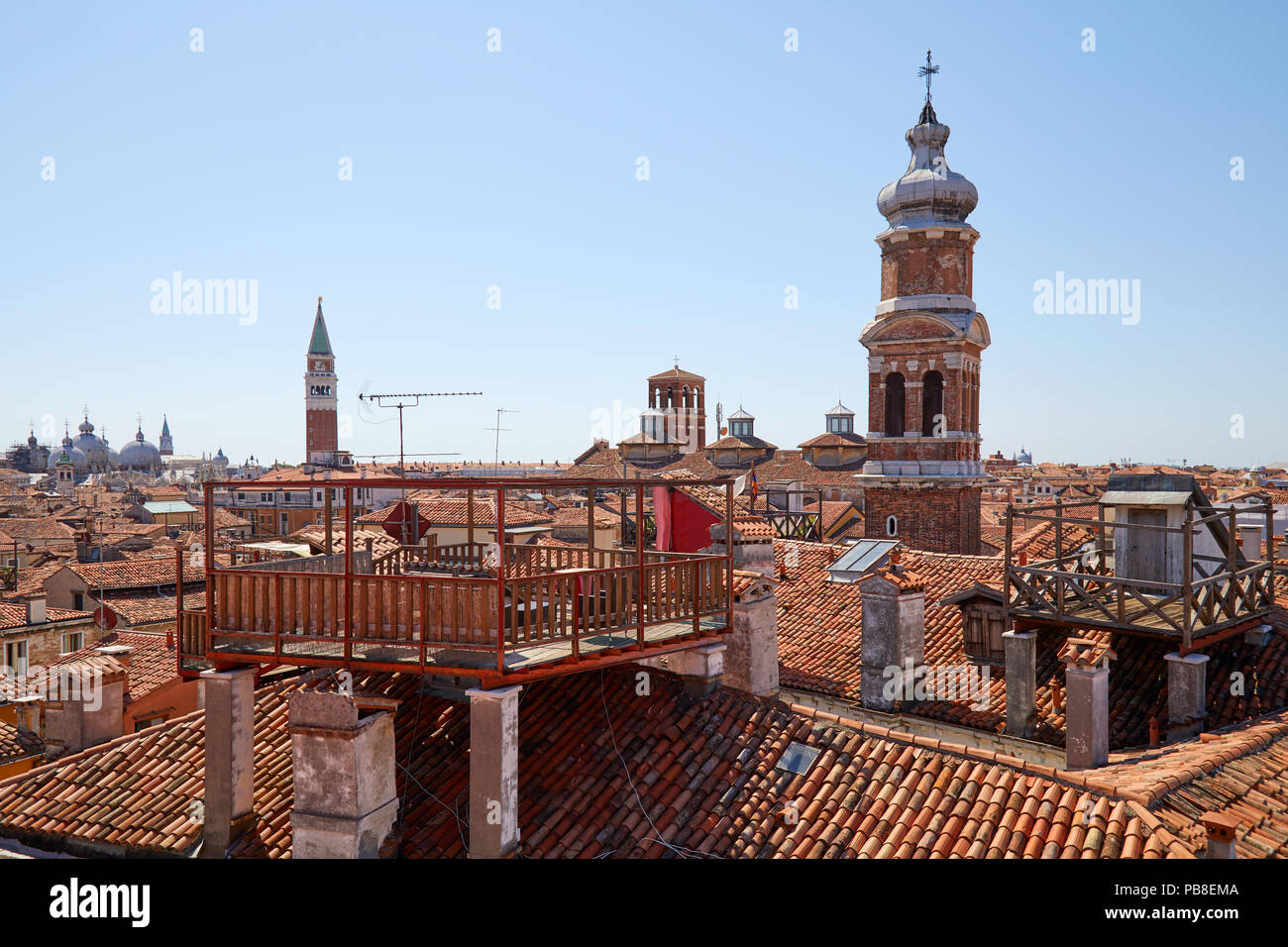Elevated view of Venice roofs with typical altana balcony and San Marco bell tower in summer, Italy - Stock Image