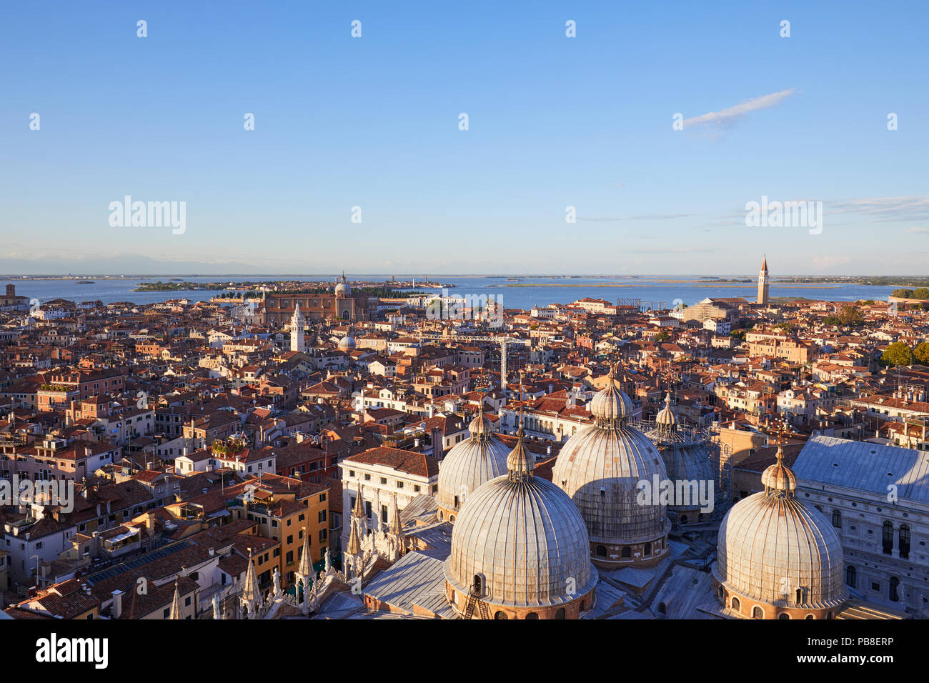 Elevated view of Venice with basilica domes and rooftops from San Marco bell tower before sunset, Italy Stock Photo