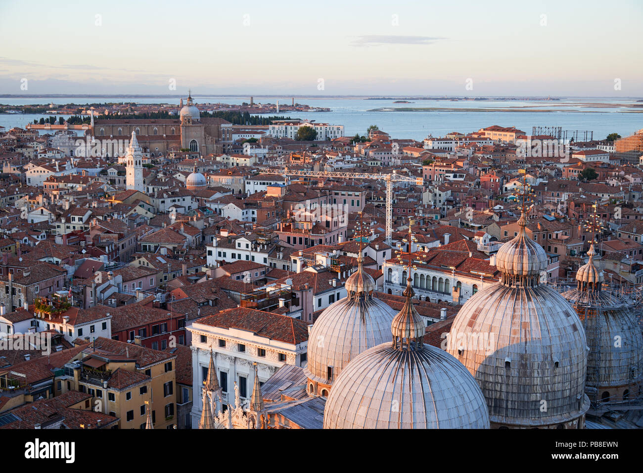 Aerial view of Venice rooftops and Saint Mark Basilica domes before sunset, Italy - Stock Image
