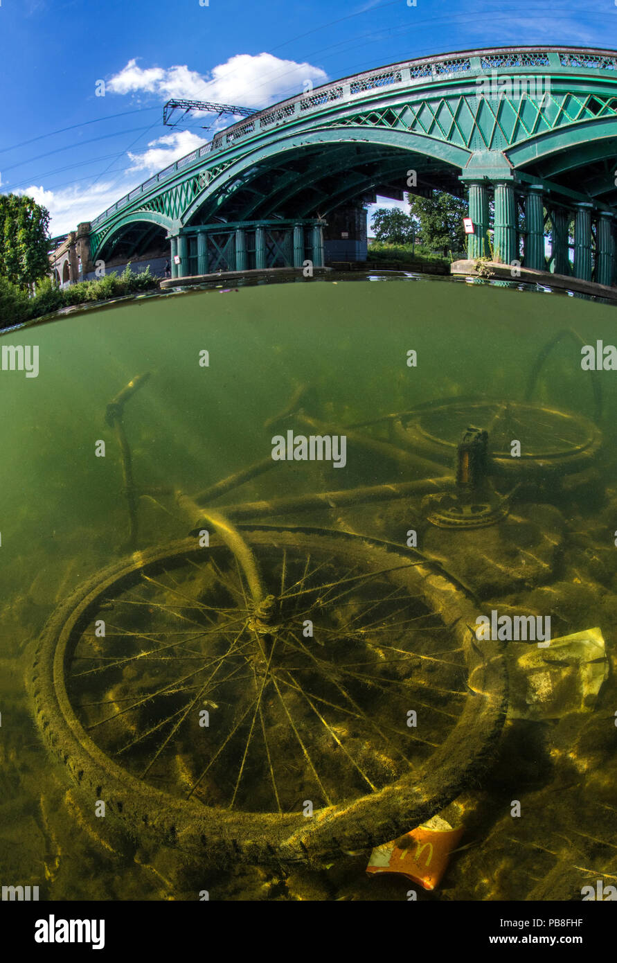 Discarded bicycle in the River Nene, Peterborough, Cambridgeshire, England. UK August.  The bridge was build by William Cubitt in 1850 and is the only cast iron bridge still in use on a major high speed train line. - Stock Image