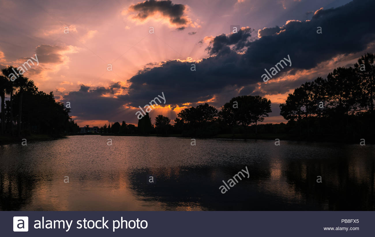 Sunset with sunrays at the pond behind the mall. - Stock Image