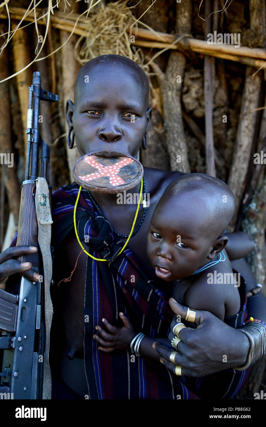 Mursi woman with clay lip plate, holding rifle and son. Mago National Park. Omo Valley, Ethiopia. - Stock Image