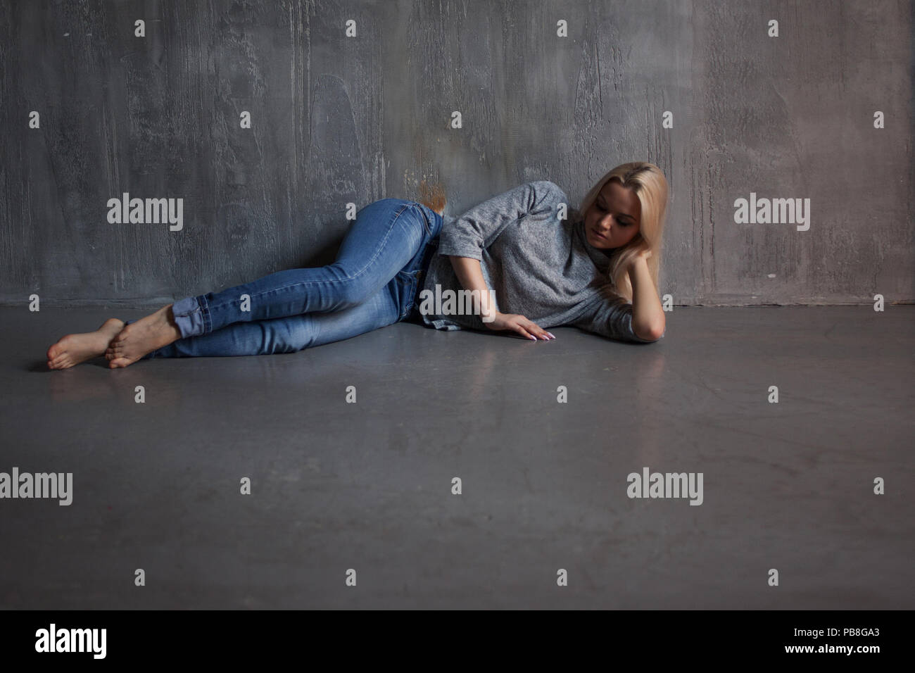 Depression. Young woman lying on the floor, concept of stress or post-traumatic disorder - Stock Image