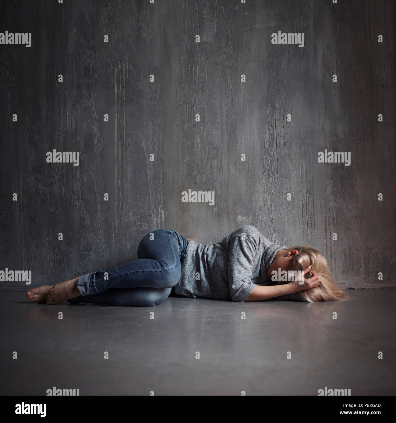 Depression. Young woman lying on the floor covering head with hands, concept of stress, copy space on the top - Stock Image